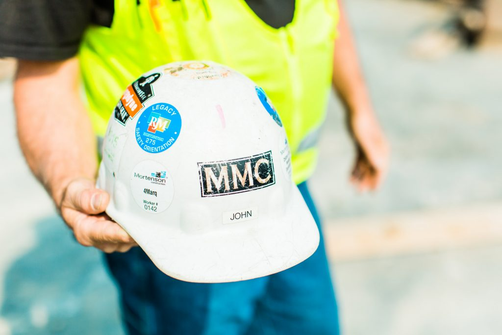 hard hat in construction workers hand during safety week