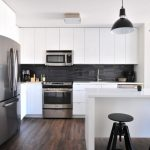 Multifamily housing apartment kitchen with white cabinets and wood floors