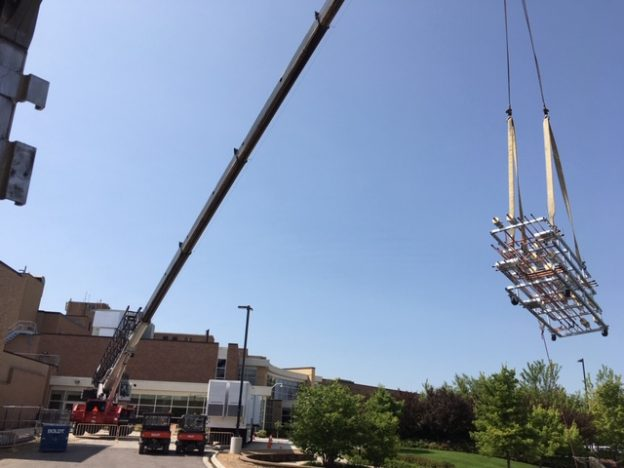 Crane hoisting HVAc prefab for healthcare facility