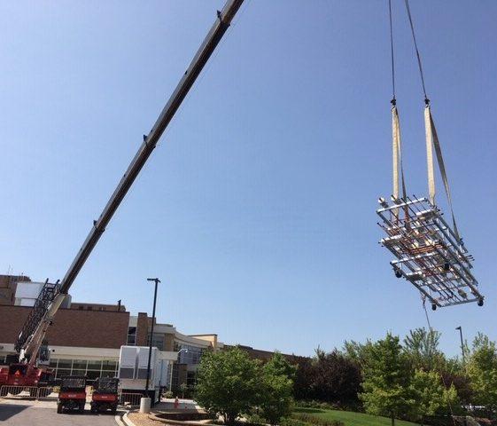 Crane hoisting HVAc prefab for healthcare facility